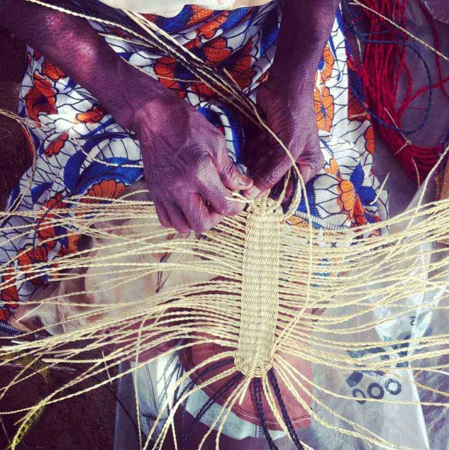 A Ghanaian artisan hand-weaving the base of an AAKS bag © AAKS