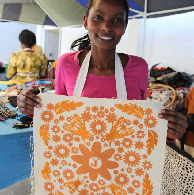Kenyan artisan proudly presenting her work on Karen Walker's embroidered and screen printed tote sold at Myer department stores across Australia. © ITC Ethical Fashion Initiative