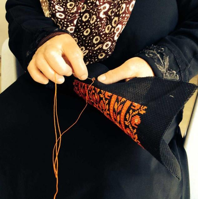 Palestinian artisan stitching a design © Chloe Mukai