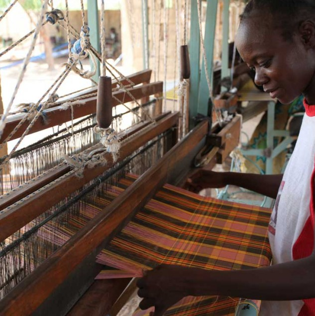 Weaver in Burkina Faso hand-weaving tartan fabric for Vivienne Westwood © Chloe Mukai